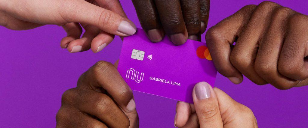 Five hands holding a purple Nubank credit card