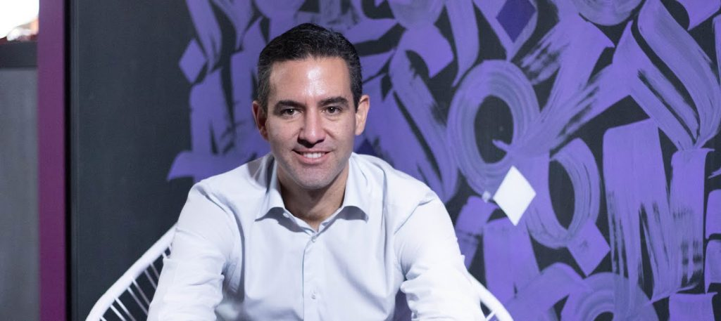 Portrait of David Vélez, founder and CEO of Nubank, sitting on a white chair with a purple and black background.