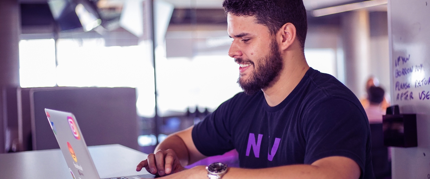 A young bearded man smiles while working with his laptop