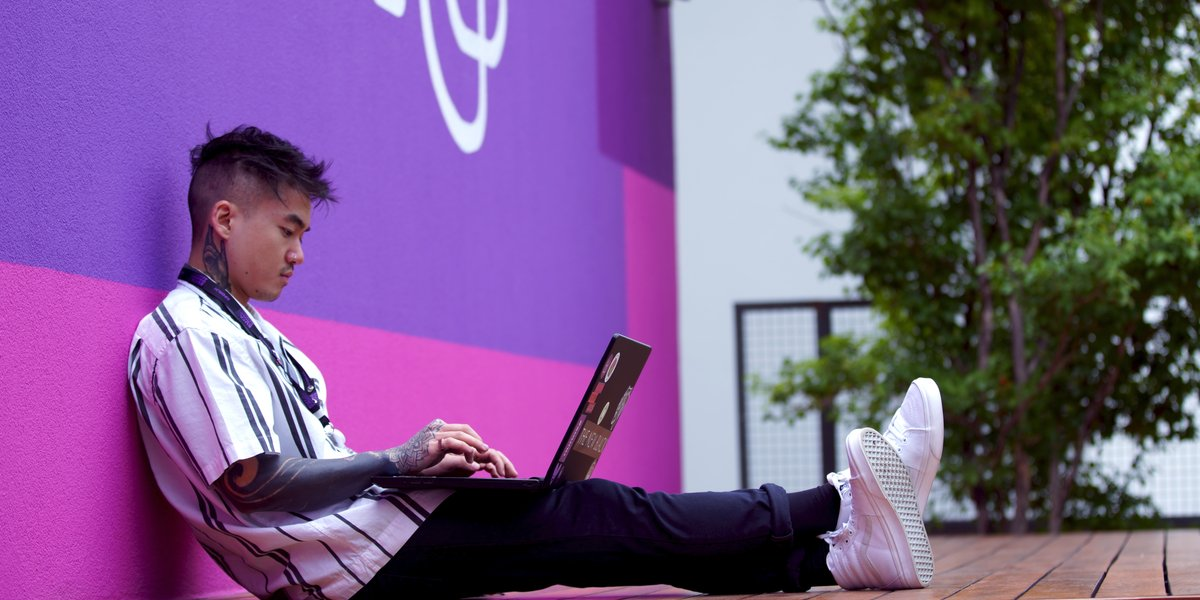 Tattooed young man using a laptop while sitting against a purple wall with Nubank's logo.