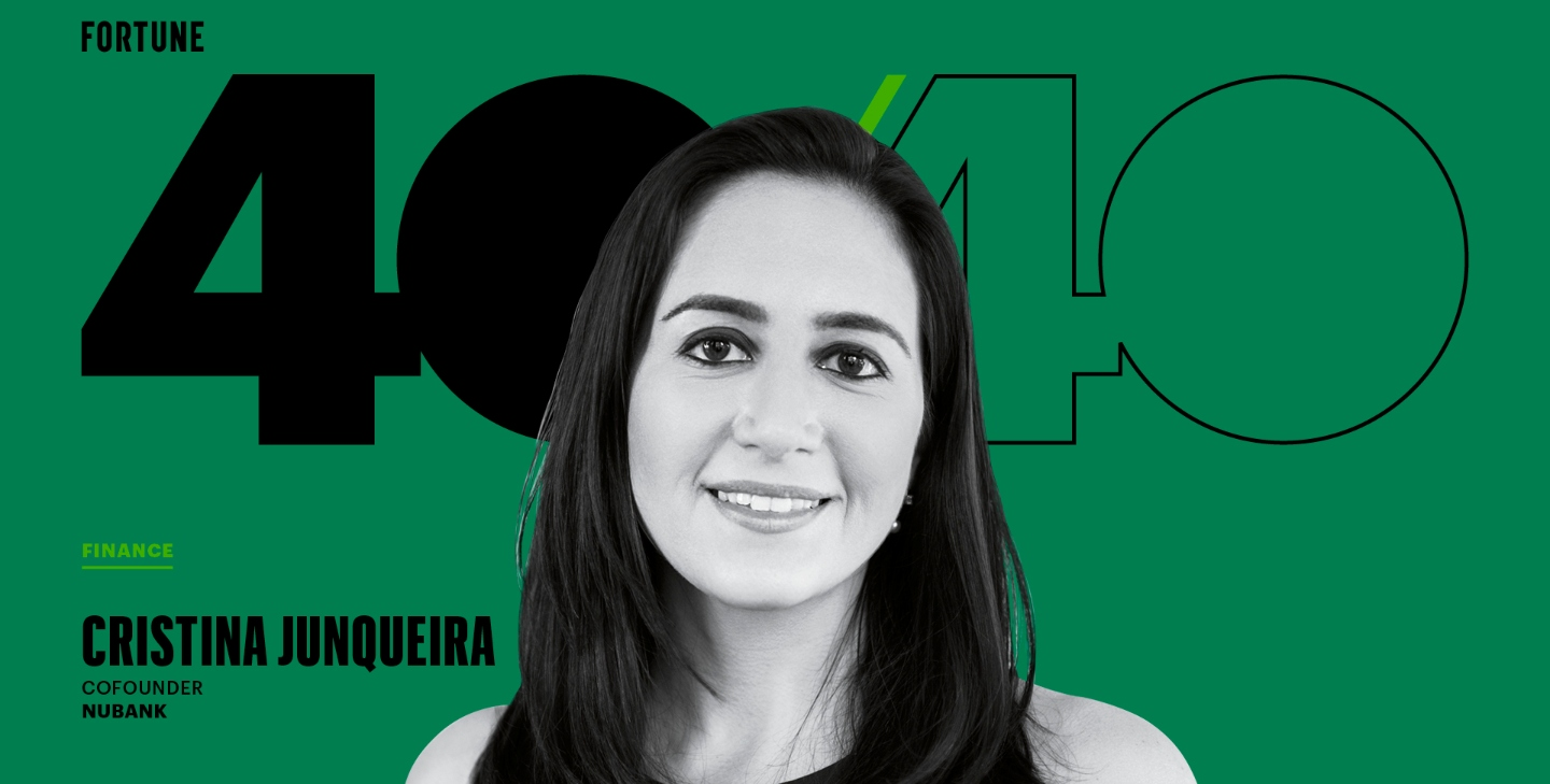 Cris Junqueira smiles in front of a green panel highlighting Fortune magazine's 2020 list of the 40 most influential leaders under 40