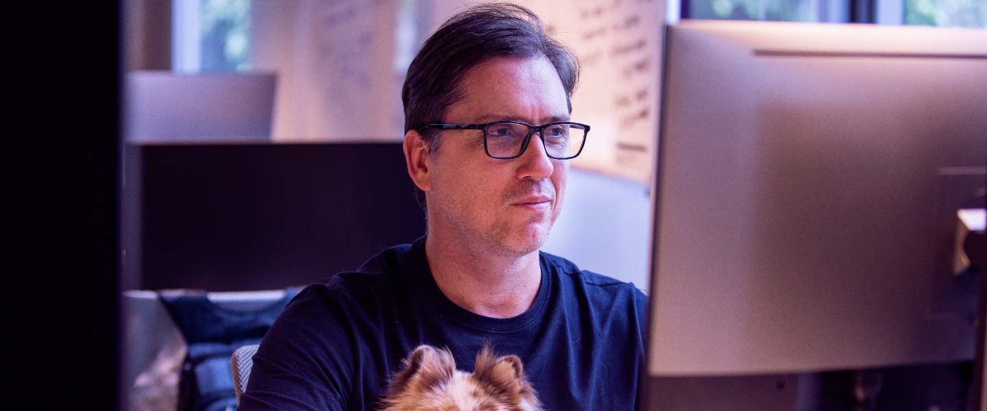 a man with glasses holds his a dog on his lap while looking at a screen