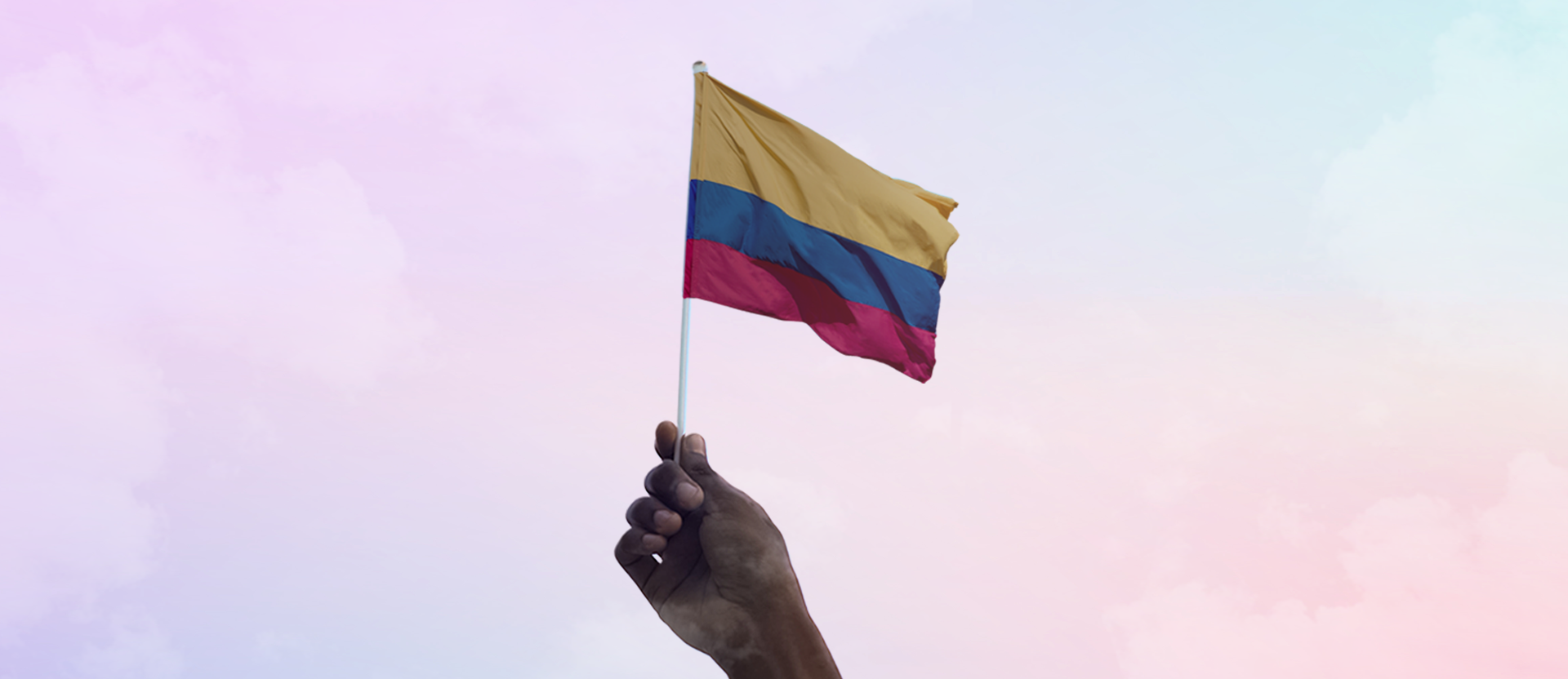 One hand holds a Colombian pennant; behind, you can see the sky