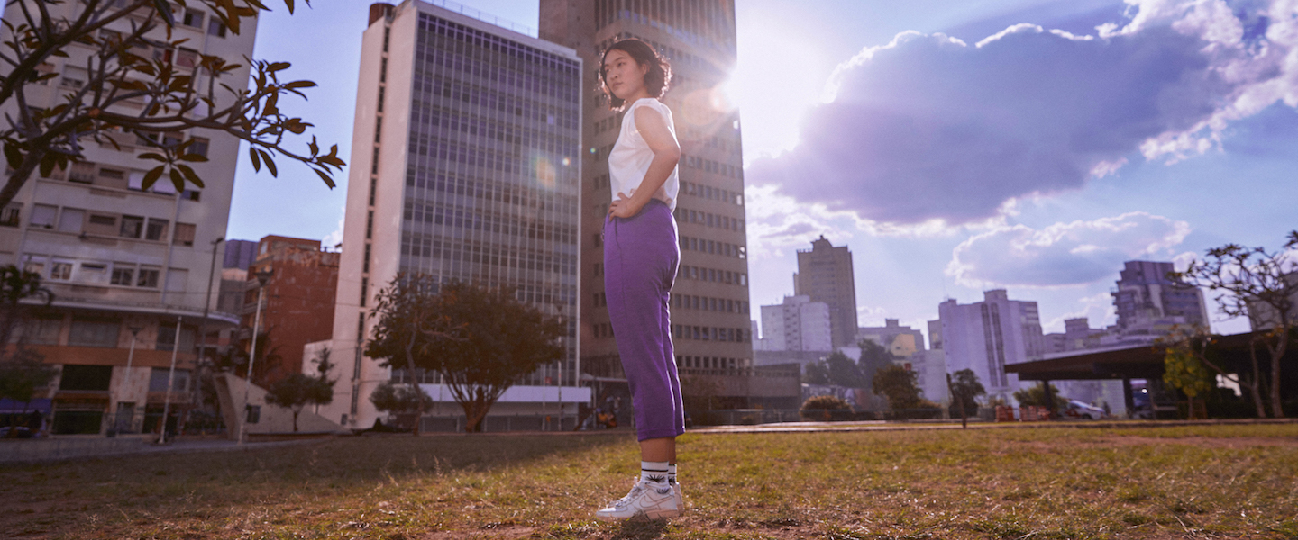 A young girl with purple trousers is pictured in a square in front of some buildings.