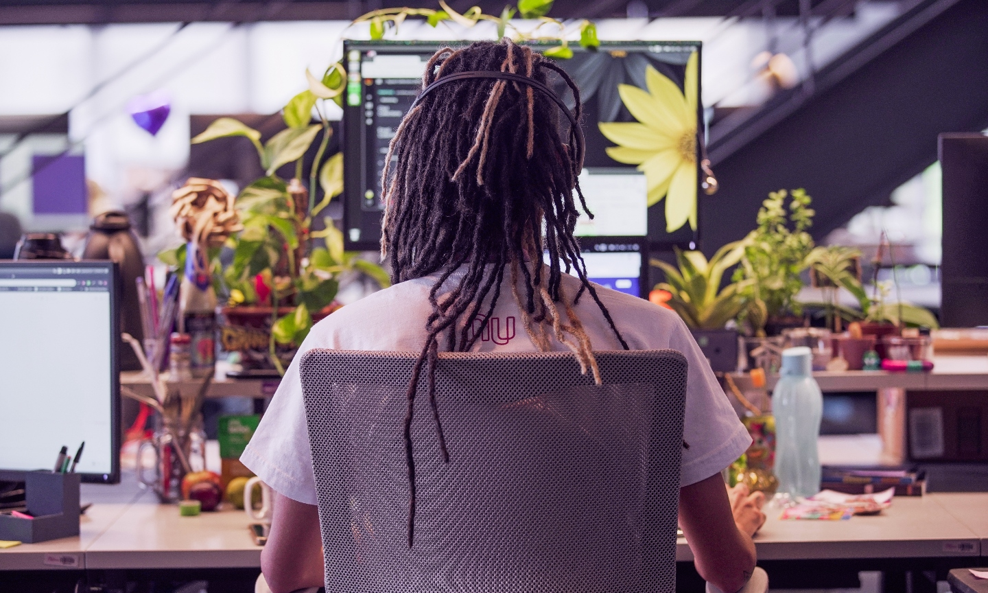 A young man with dreadlocks seen from behind works in his computer, that is surrounded by plants.