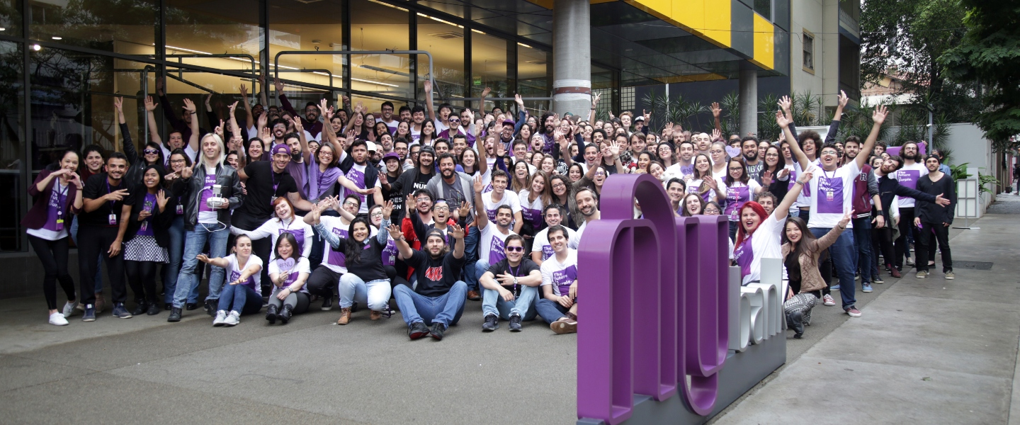 A bunch of Nubankers at the entrance of the office in Sao Paulo, Brasil, raising their hands and smiling